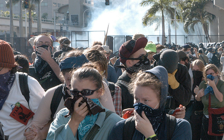 Protesters covering their faces with bandanas to protect themselves from riot police tear gas.